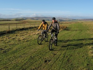 Ken and Steve riding acorss Pen y Gwely with the Berwyns in the distance.