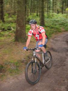 Shaun riding the cycle trail through the trees in Nercwys Forest.