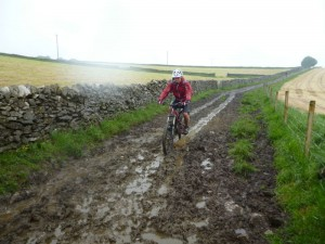 Alex on the muddy in the wet Wormhill descent.