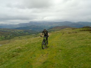 Brian climbing the the Braich with a tail wind and a stunning view of Cadair Idris behind.