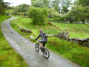 Mark climbing past derelict houses on the Sarn Helen trail.
